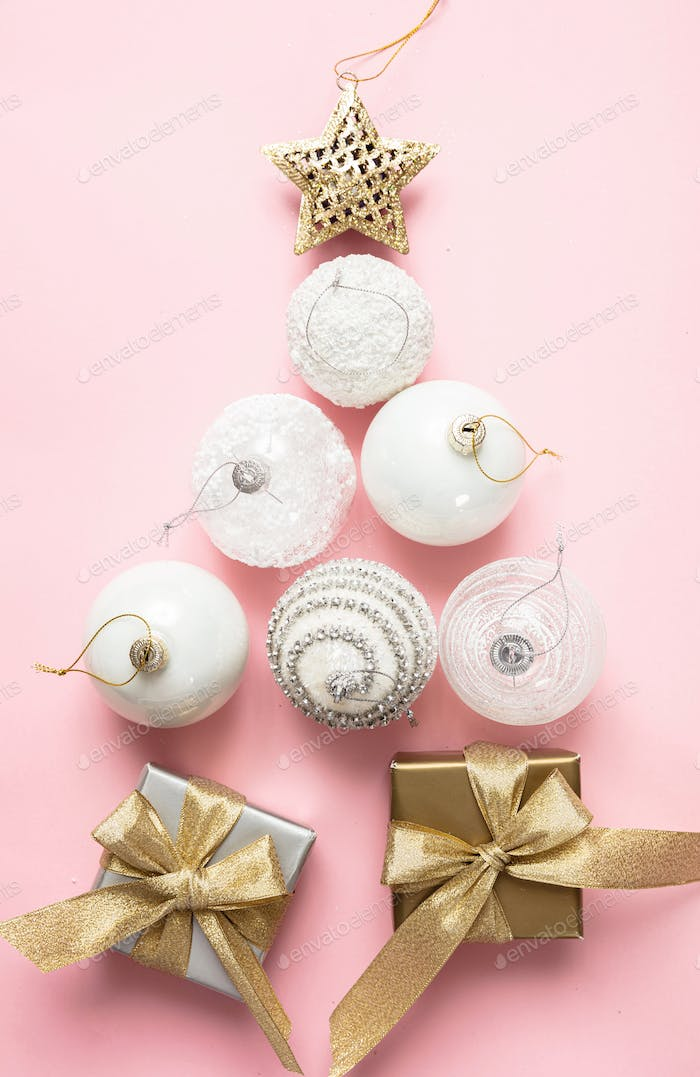 Xmas baubles in tree shape and gifts against pink background, high angle