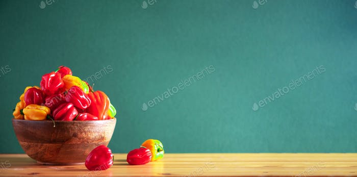 Yellow and red scotch bonnet chili peppers in wooden bowl over green background. Copy space