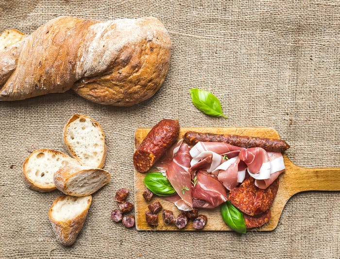 Meat appetizers selection and a loaf of rustic village bread on