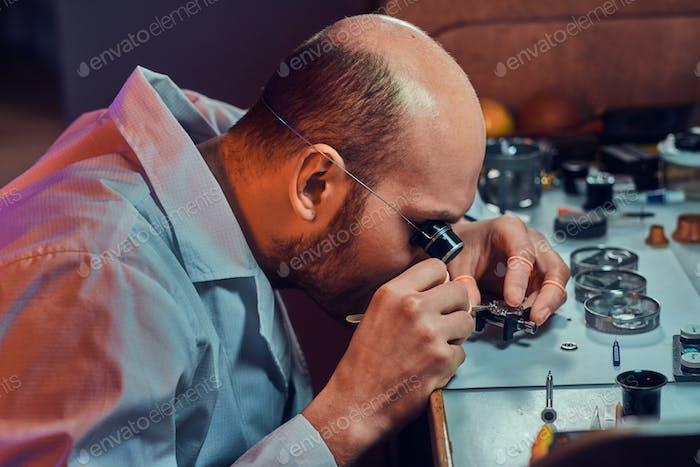 Nachdenklicher Meister arbeitet an der Uhr des Kunden in seiner Werkstatt.