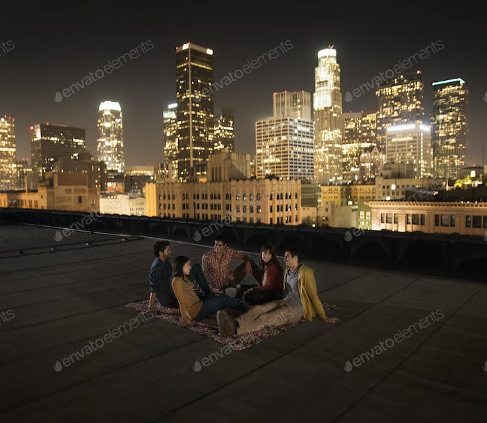 A group of friends gathered on a rooftop overlooking a city lit up at night.