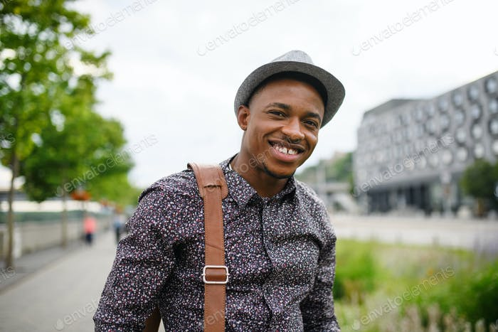 Fröhliche junge schwarze Mann Pendler im Freien in der Stadt, zu Fuß