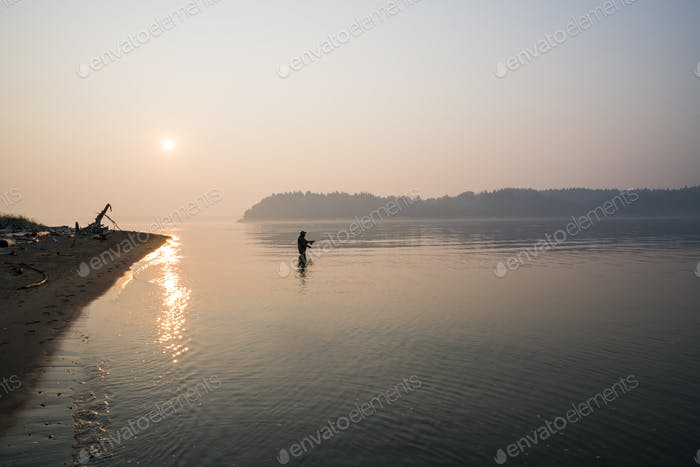 Silhouette of fisherman fly fishing for salmon and sea-runt cutthroat trout in Puget Sound near Port
