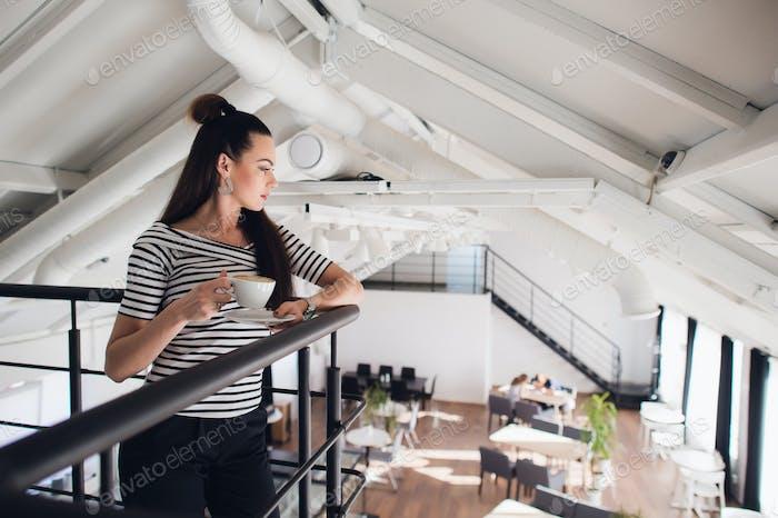 Привлекательная молодая женщина с длинными прямыми волосами holind чашкой капучино и глядя в сторону.