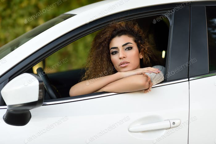 Young arabic woman inside a white car looking through the window