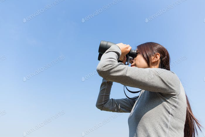 Asian Young woman use of the binoculars with clear blue sky