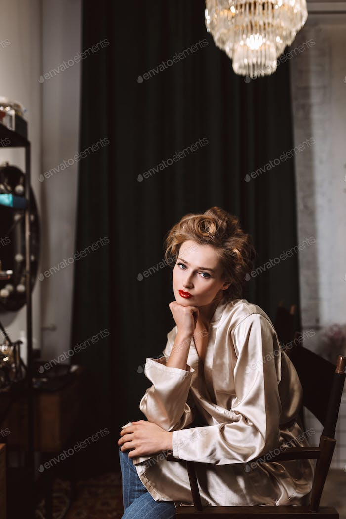 Young beautiful actress with wavy hairstyle and red lips in silk