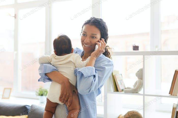 Junge Mutter im Gespräch am Telefon während halten Baby