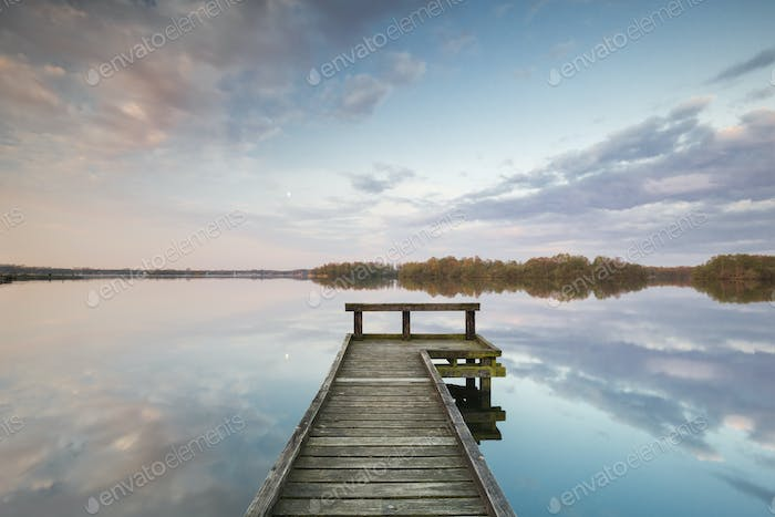 wooden pier on big lake with sky reflected