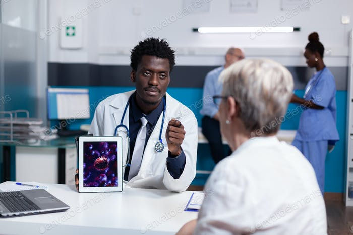 Doctor of african american ethnicity holding digital tablet