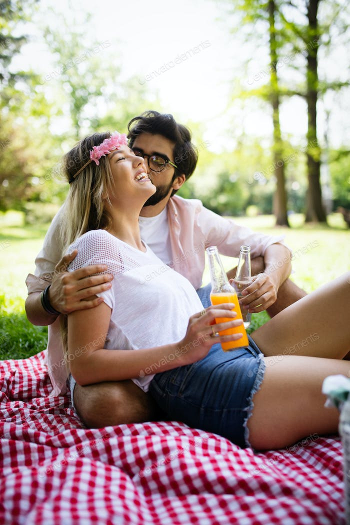 Happy young couple enjoying picnic in park