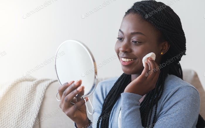 Schwarze Frau hält Spiegel und Reinigung Gesicht mit Wattepads
