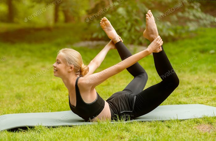 Flexible blonde lady doing bow yoga pose during her outdoor class at park