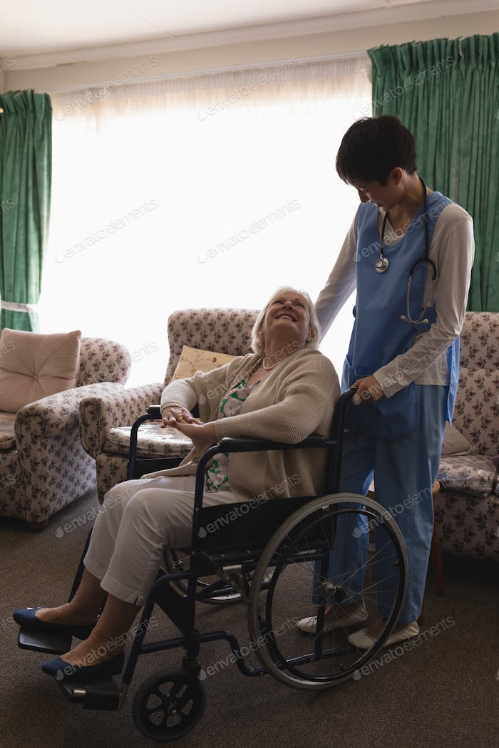 Female doctor interacting with disabled senior woman on wheelchair