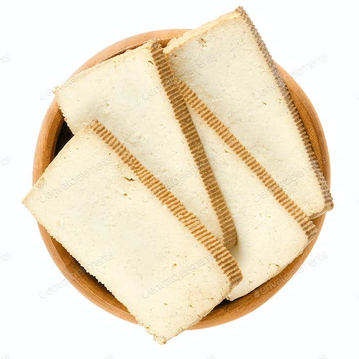 Smoked tofu slices in wooden bowl