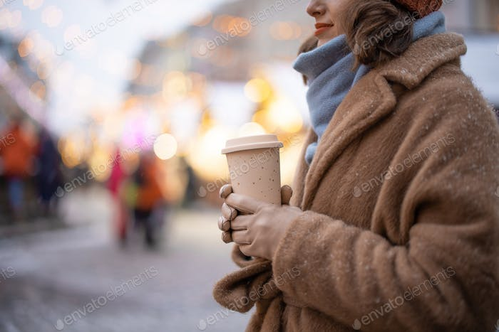Woman with takeaway coffee on the Christmas market