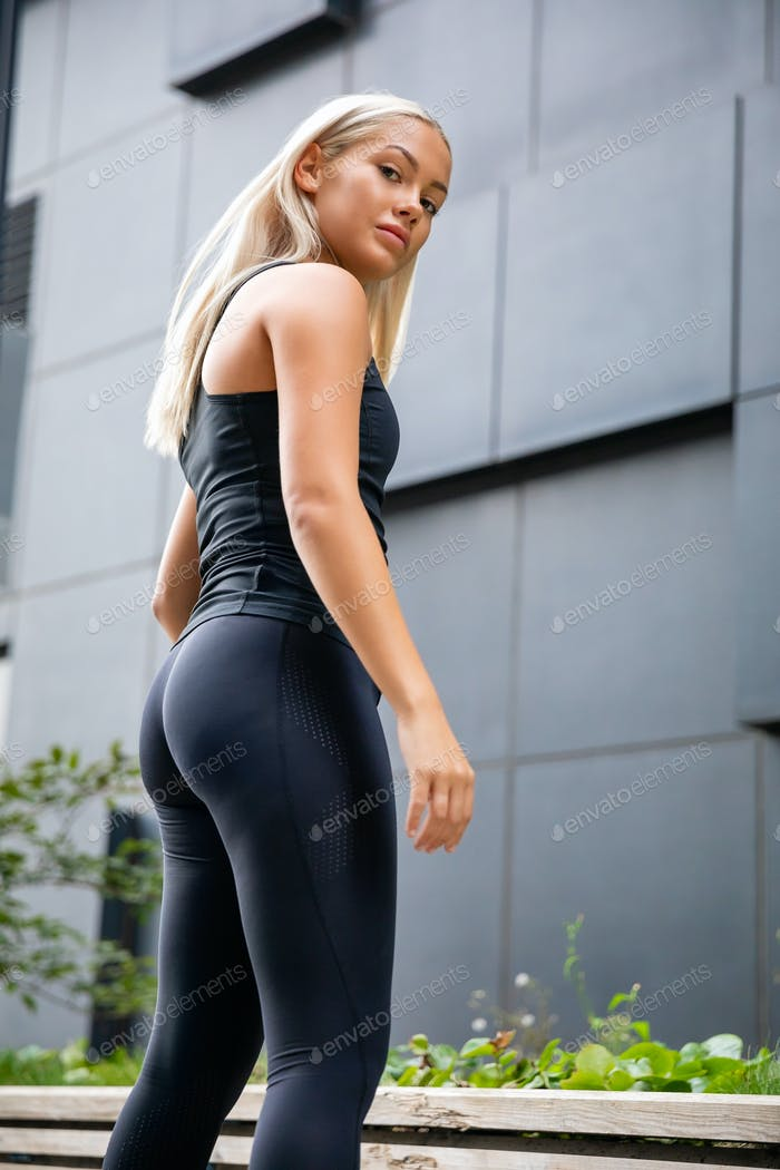 Confident and determined Female Athlete Standing Against Building