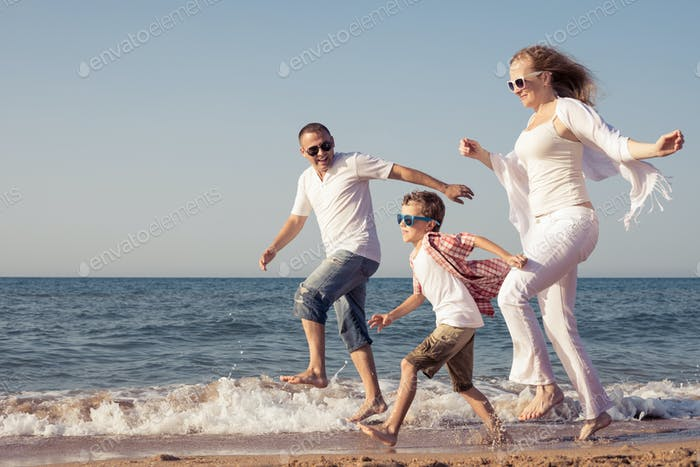 Happy family running on the beach at the day time.