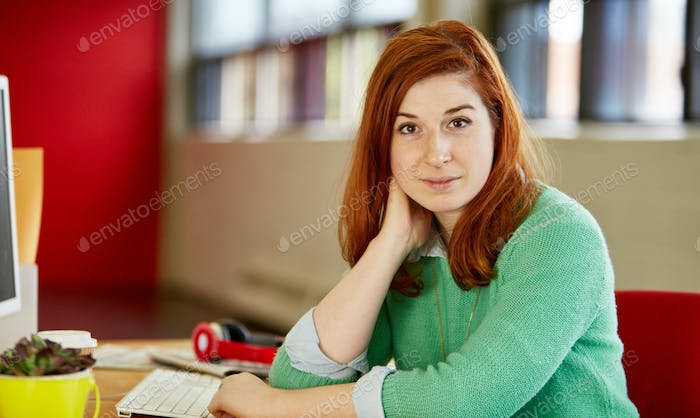 Confident female designer working at her desk in red creative of