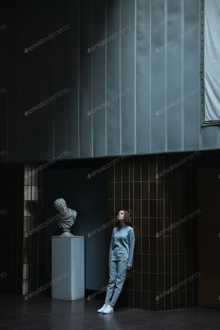 Woman leaning against a dark wall in an art gallery