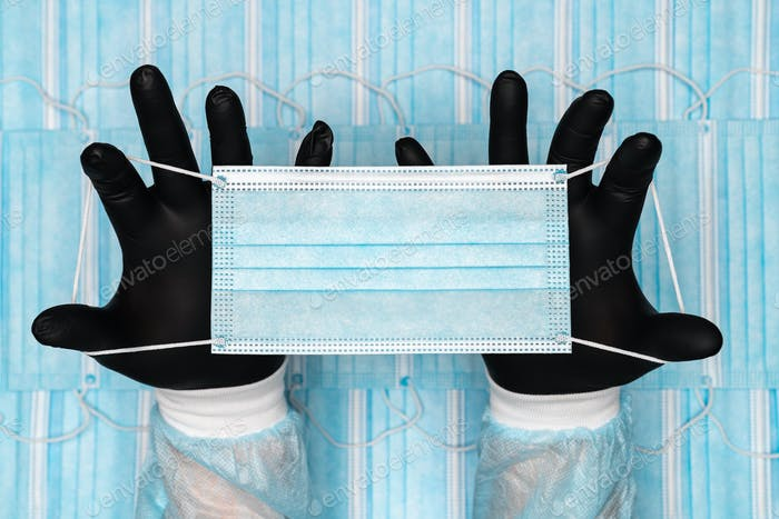 Doctor Holding Blue Surgical Medical Face Mask in Two Black Protective Glove in Hands