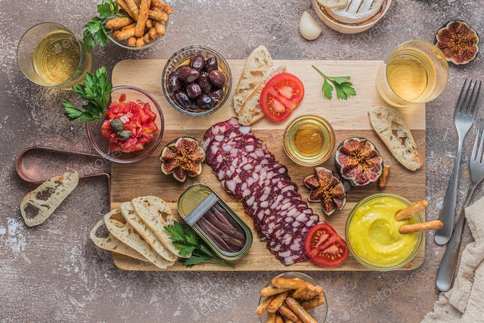 Salami, cheese, anchoves, bread and alioli dip on wooden board, flat lay
