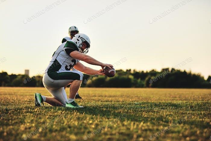 American Football-Spieler üben Platz treten auf einem Feld