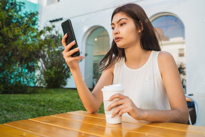 Young woman using her phone at coffee shop.