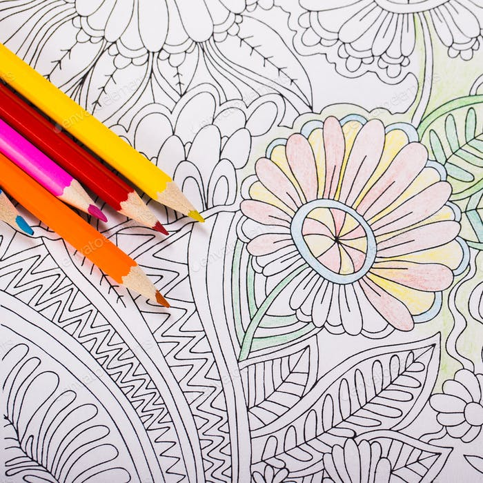 Multi-colored pencils and coloring book for adults