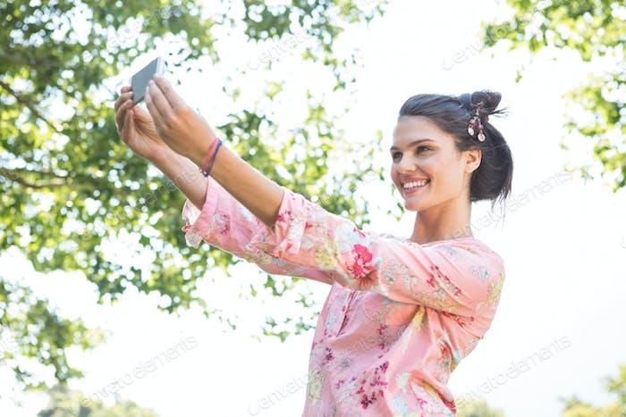 Pretty brunette taking a selfie on a summers day