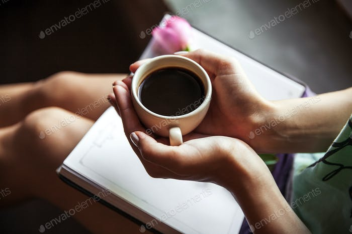 Girl reading book and drinking coffee, beautiful rose. Morning, hobbies, flowers, study