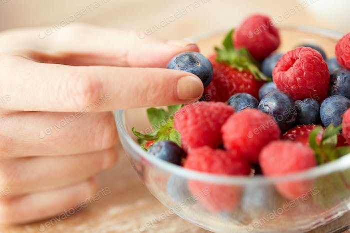 close up of young woman hand with berries in bowl