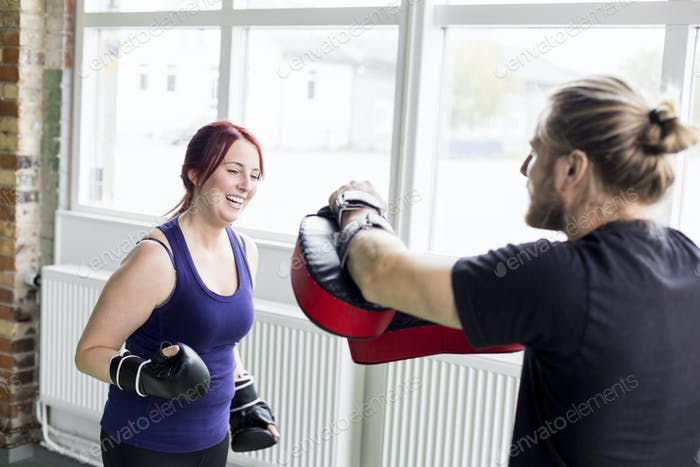 Young woman with male trainer practicing boxing in health club