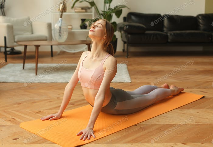 Fitness-Frau in Sportbekleidung in Yogakobra-Pose auf Yogamatte