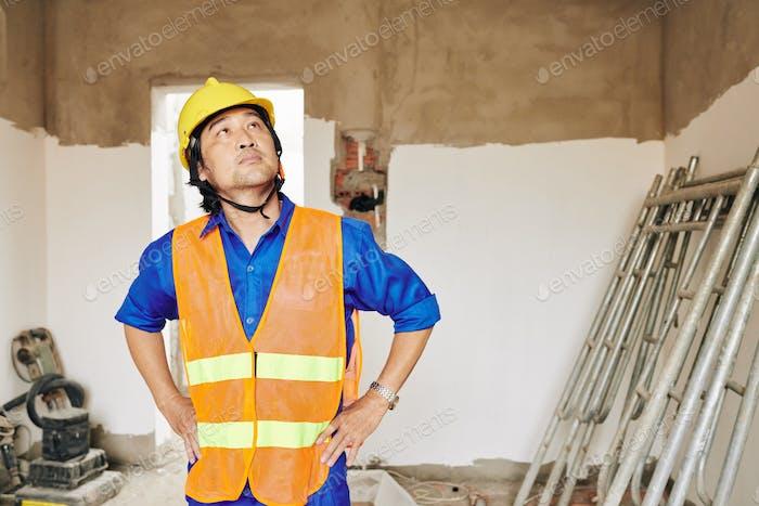 Pensive builder looking at room ceiling