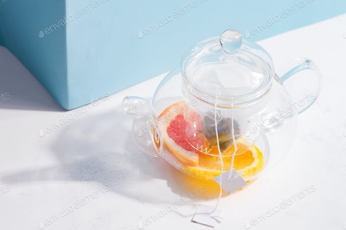 Summer homemade cold fruit tea drink in a glass transparent teapot on a white table with shadow