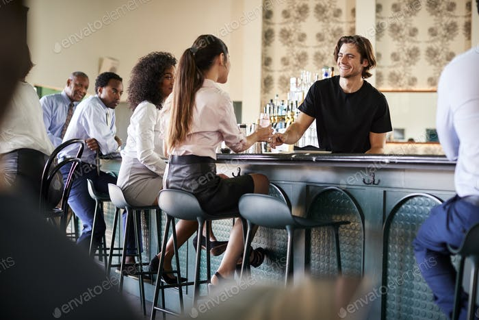 Bartender Serving Two Businesswomen Meeting For After Works Drinks