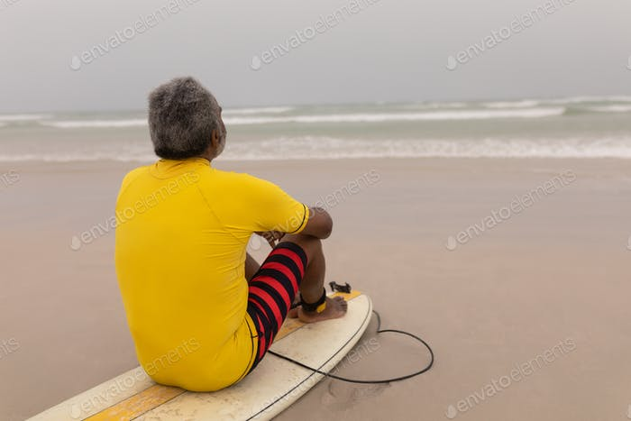 Rear view of senior male surfer sitting on the surfboard on beach