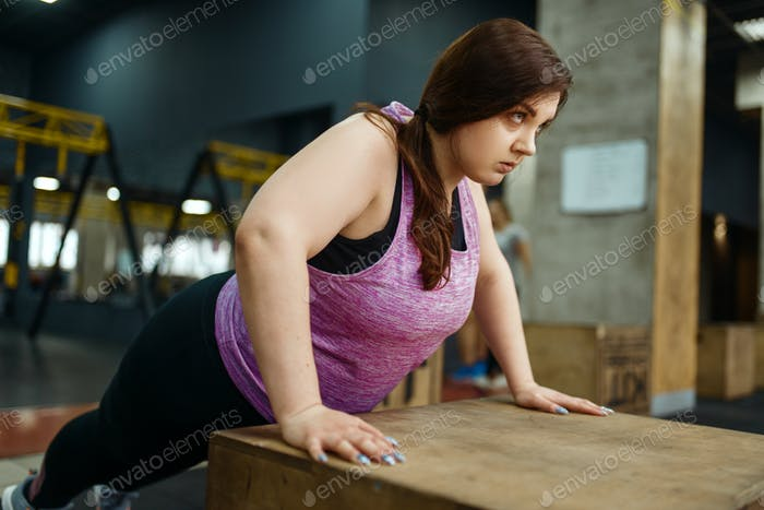 Overweight woman doing push ups exercise in gym