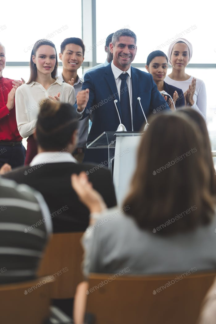 Businessman standing on podium with diverse colleagues while he speaks at business seminar in office
