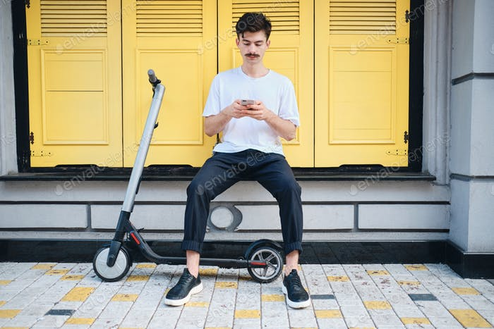Young mustache man with e-scooter thoughtfully using cellphone over yellow background on city street