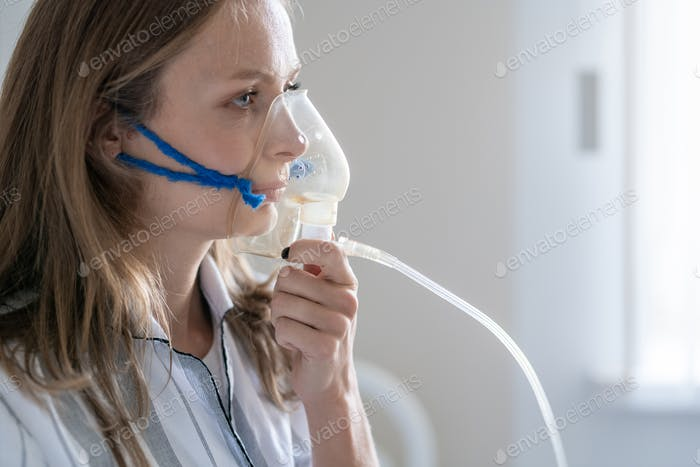 Sick young female patient holding oxygen mask by her mouth and nose
