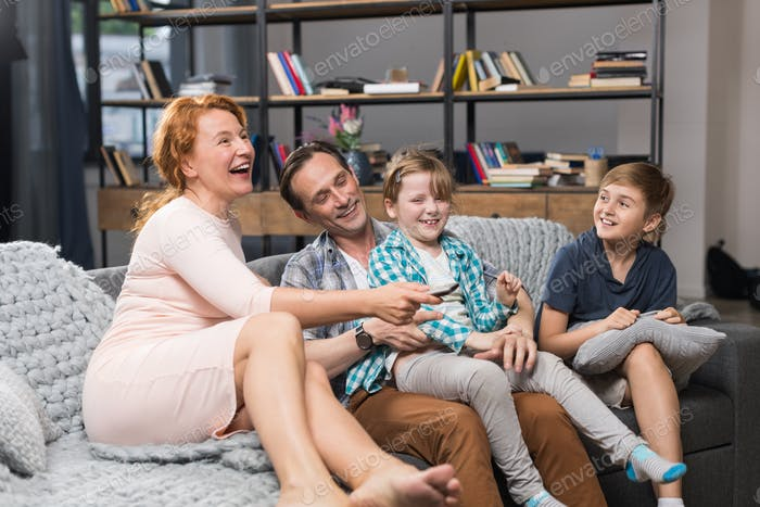 Family Sitting On Couch Watching TV, Happy Smiling Parents Spending Time With Children
