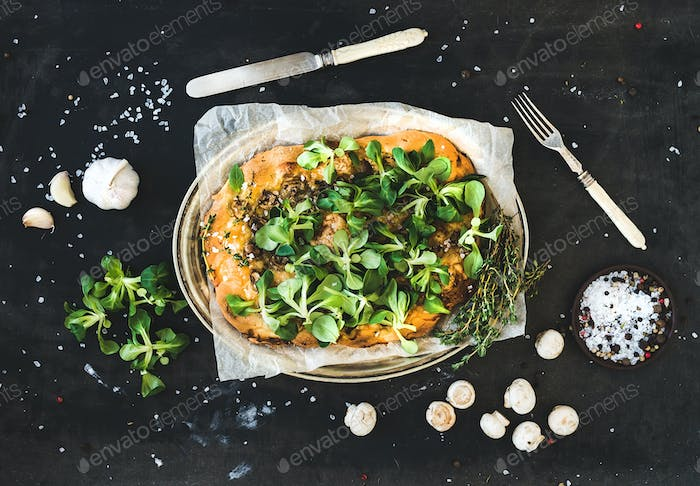 Rustic homemade pizza with fresh lamb's lettuce, mushrooms and garlic over dark grunge background