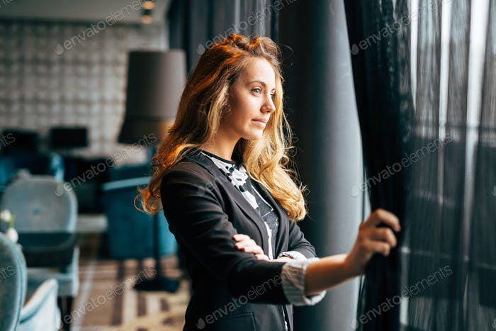 Pensive beautiful businesswoman looking through window