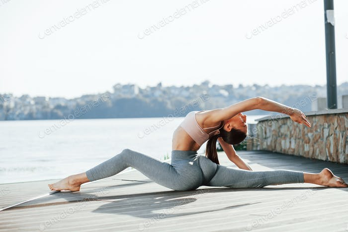 Conception of bodycare. Young woman does exercises against lake