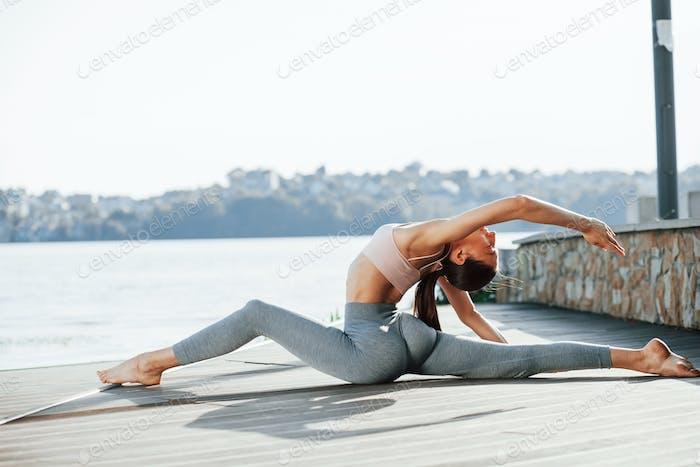 Konzeption der Körperpflege. Junge Frau macht Übungen gegen See