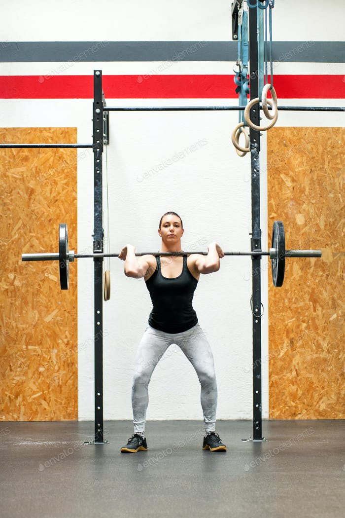 Young woman doing a front squat in a gym