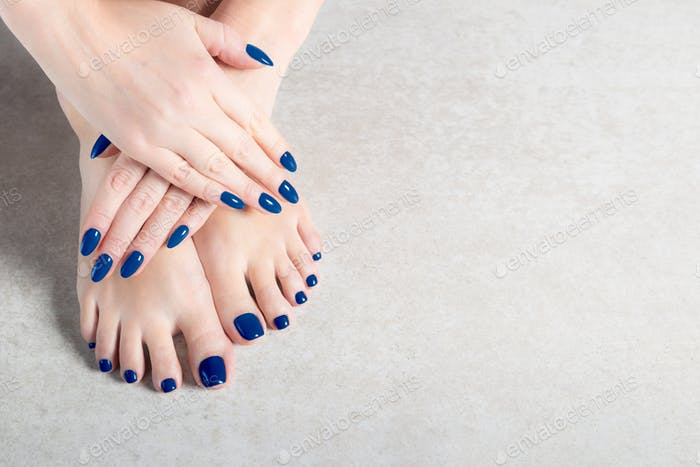 Young lady is showing her blue manicure and pedicure nails