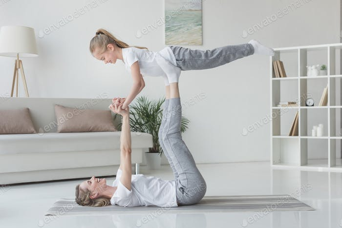 mother and daughter practicing acro yoga at home